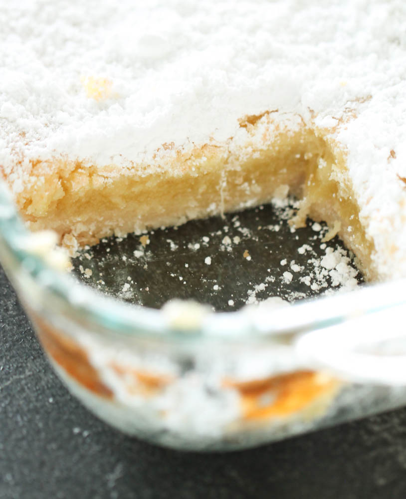 Lemon bars in pan topped with powered sugar