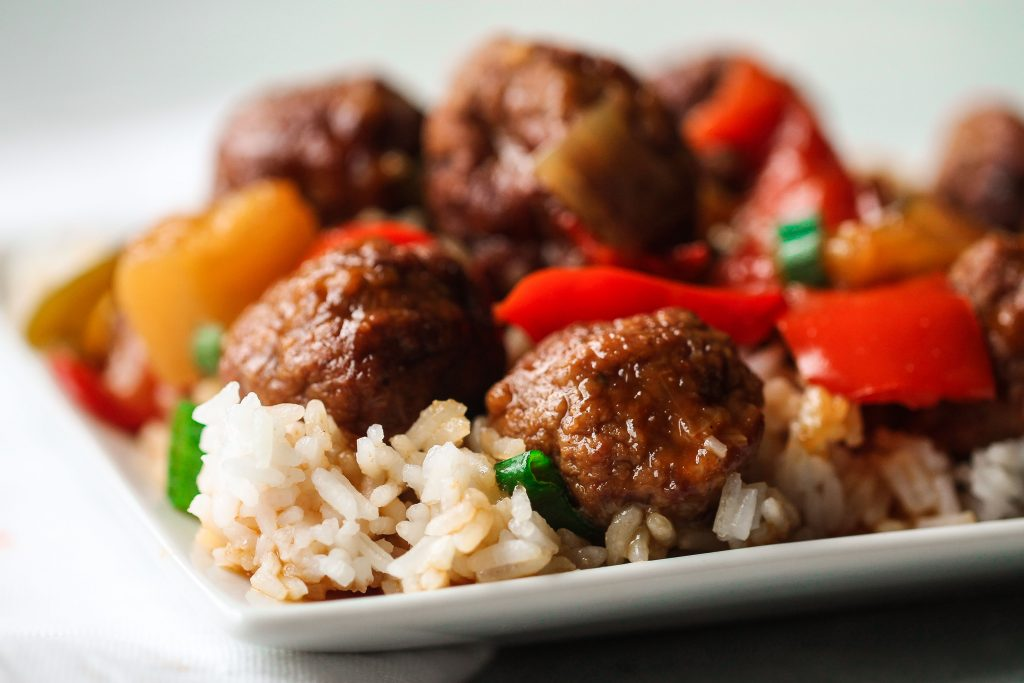 sweet and sour meatballs on bed of rice with veggies