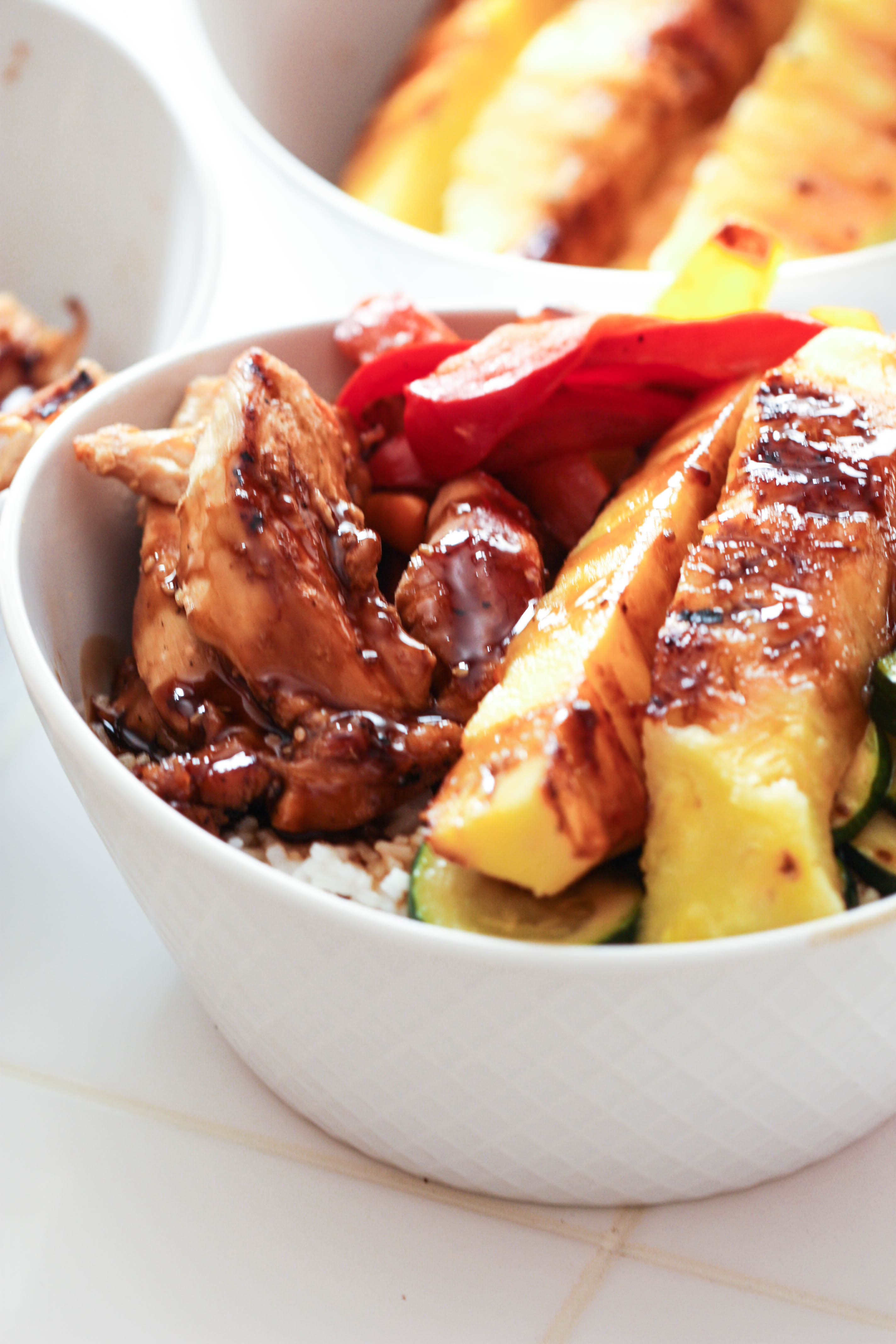 Finished Hawaiian Chicken Rice Bowls with teriyaki sauce drizzled on top