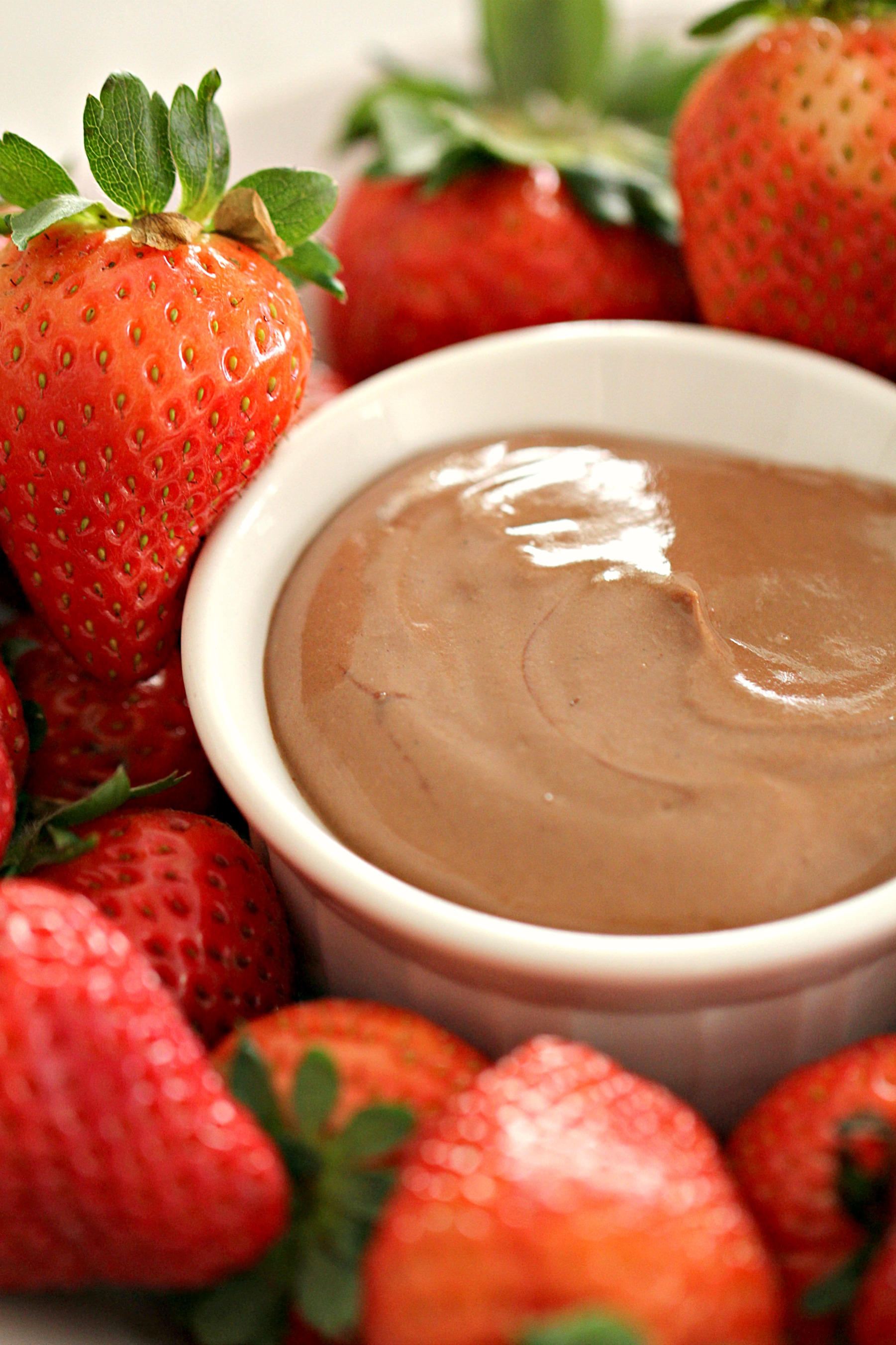 chocolate yogurt fruit dip in a white bowl surrounded by strawberries