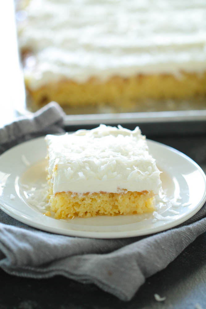 a slice of Sheet Pan Hawaiian Poke Cake with sprinkled coconut on a white plate