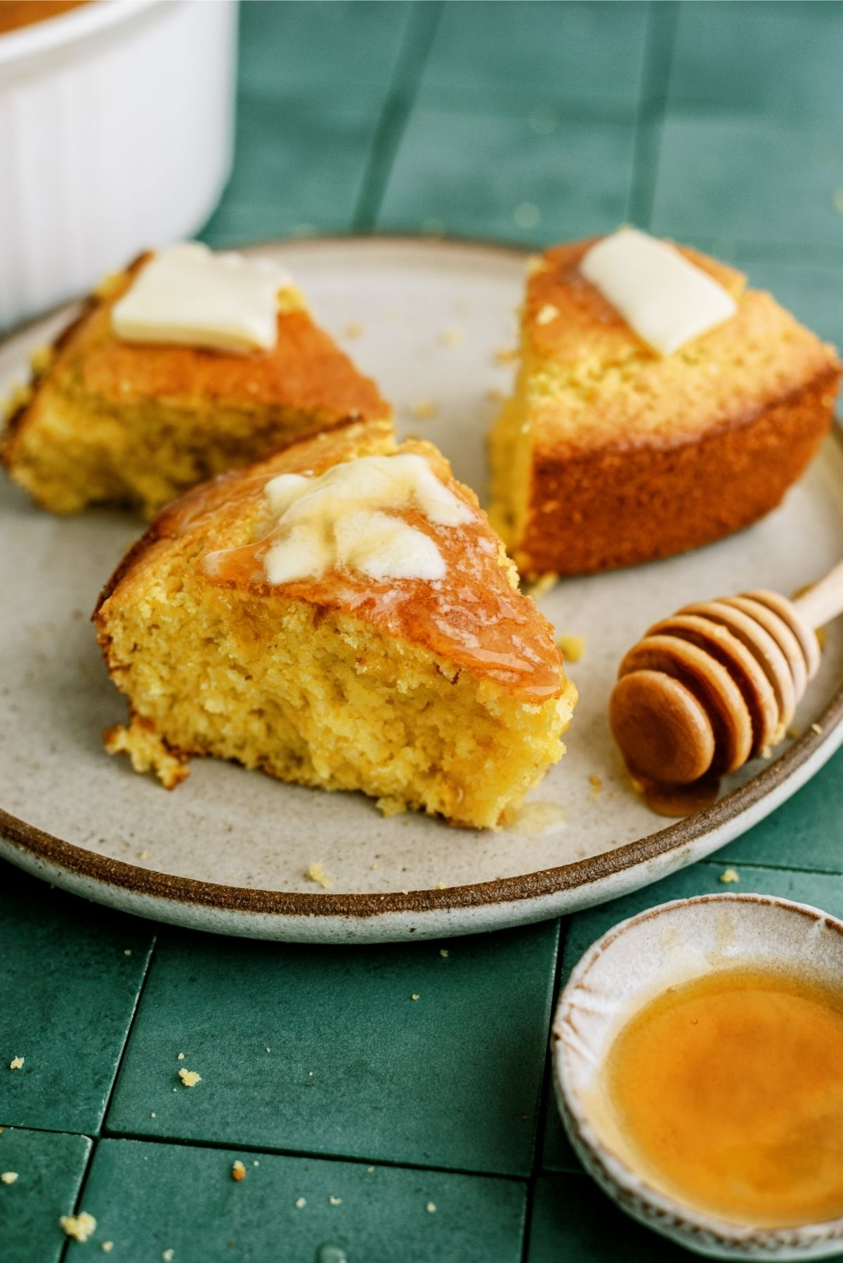 Easy Homemade Cornbread sliced on a plate, topped with butter and honey