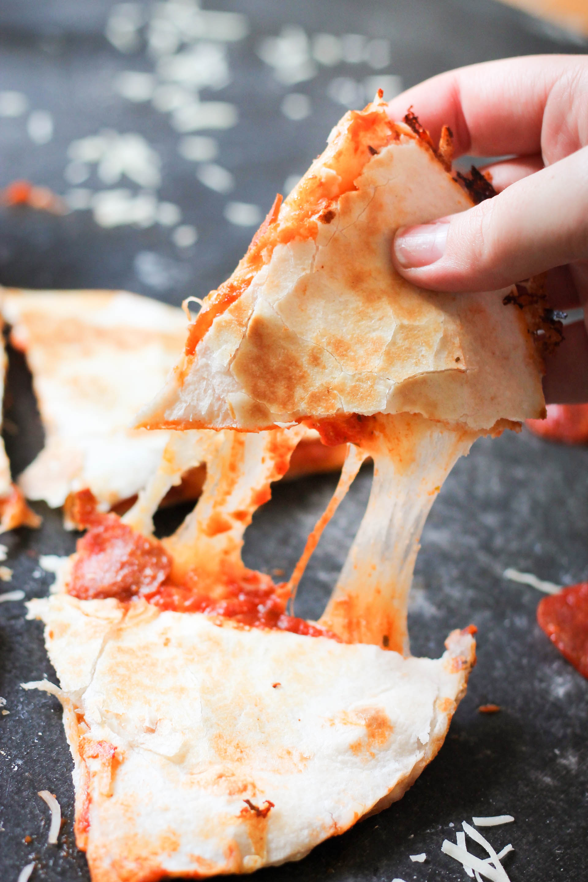 a triangle of easy pizza quesadillas being pulled apart to show gooey, melty cheese