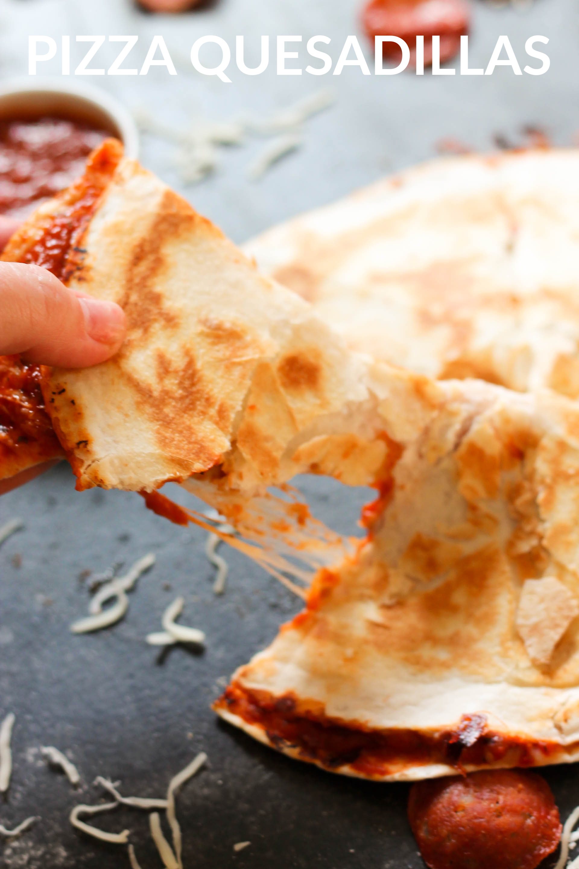 easy pizza quesadillas that have been cooked cooked, with a hand pulling out a triangle slice to eat