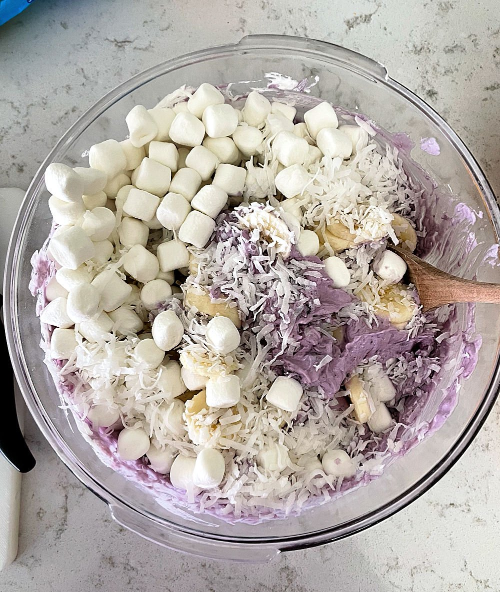 Ingredients for Blueberry Fluff Salad in a glass mixing bowl with a wooden spoon
