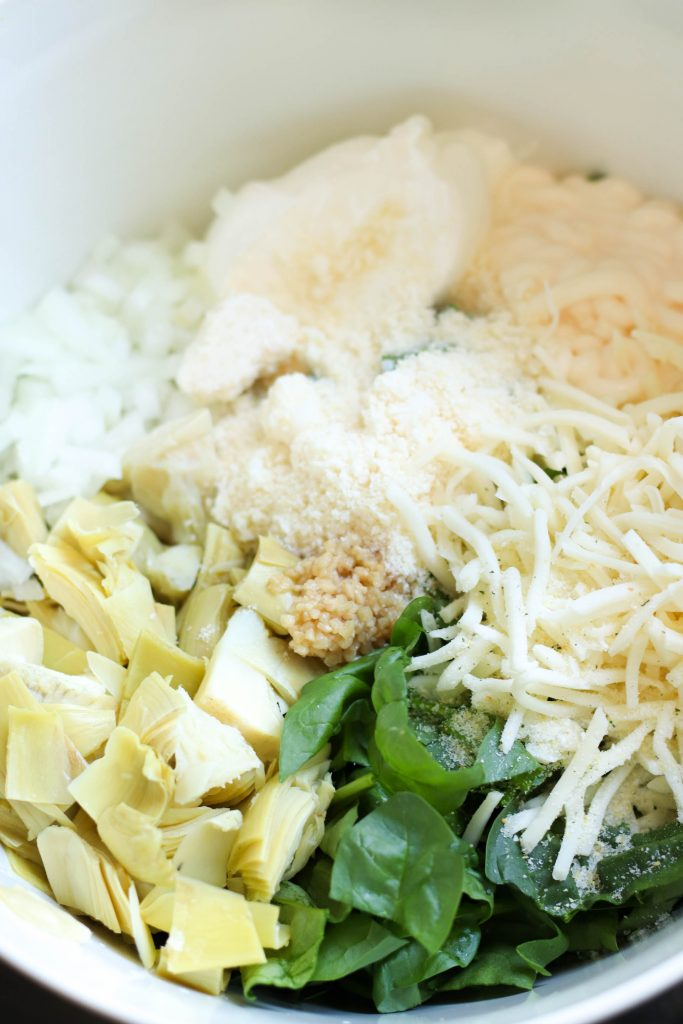 cheese, onion, spinach, artichokes, and garlic ready to be mixed together in a bowl