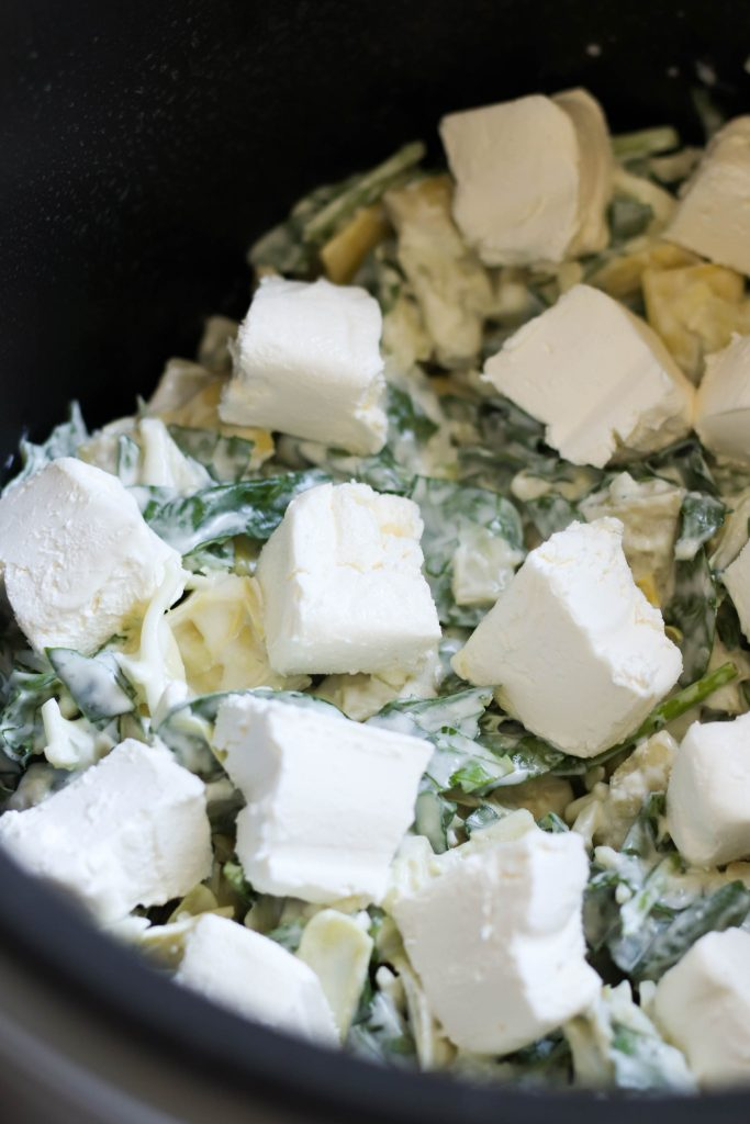 spinach artichoke dip topped with cream cheese in a slow cooker ready to be cooked