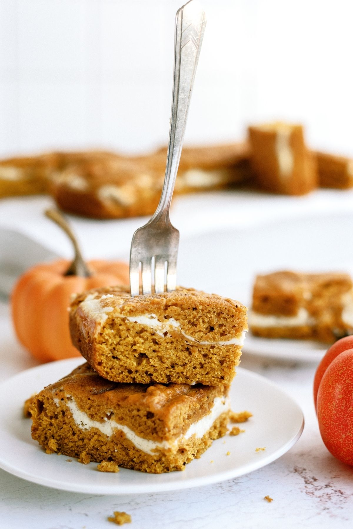 Cream Cheese and Pumpkin Roll Bars on a plate with a fork in them