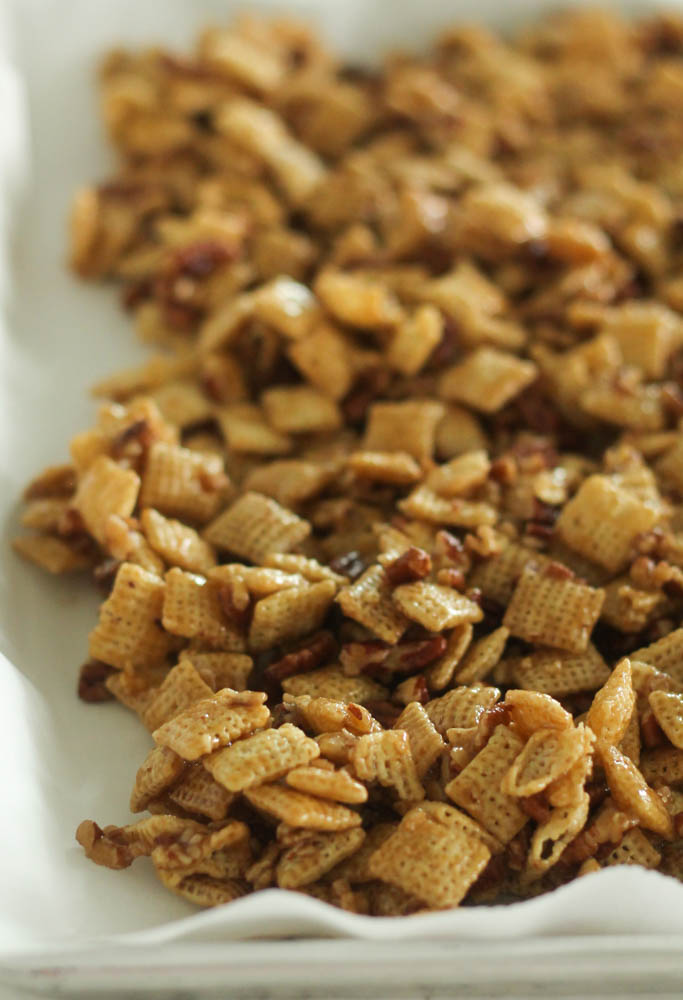 caramel chex mix spread out on a baking sheet covered in wax paper
