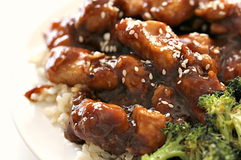 Instant Pot EASY Sesame Chicken and Rice on a white plate sprinkled with sesame seeds