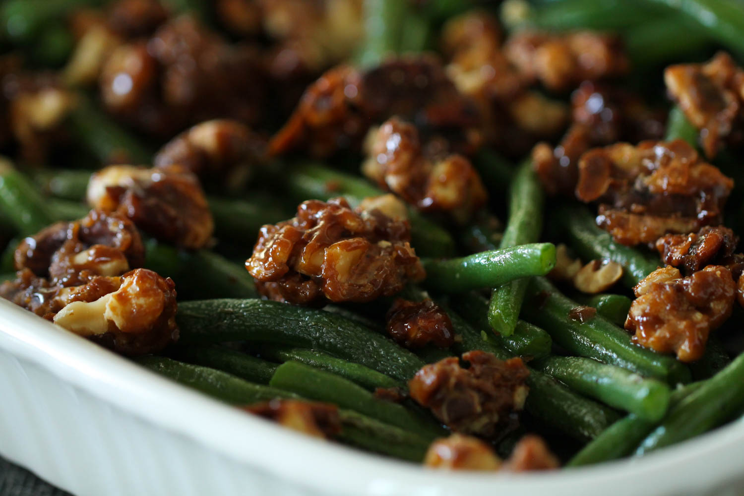cooked green beans topped with candied pecans in a white dish