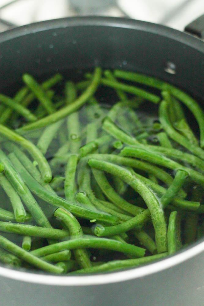 Fresh green beans sauteing in a pot