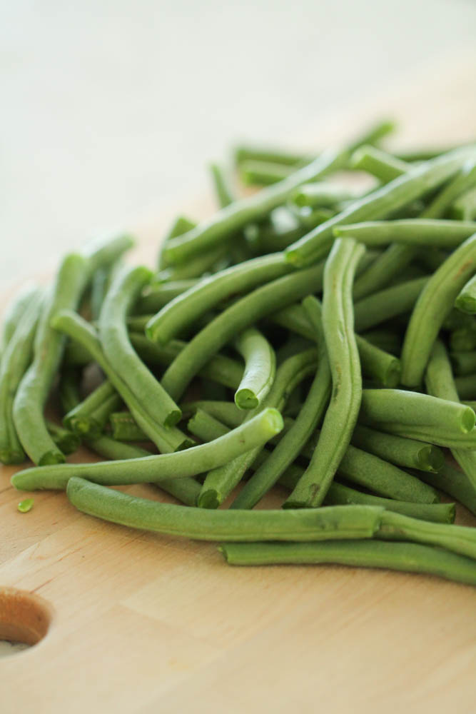 fresh green beans on a cutting board with their ends trimmed off