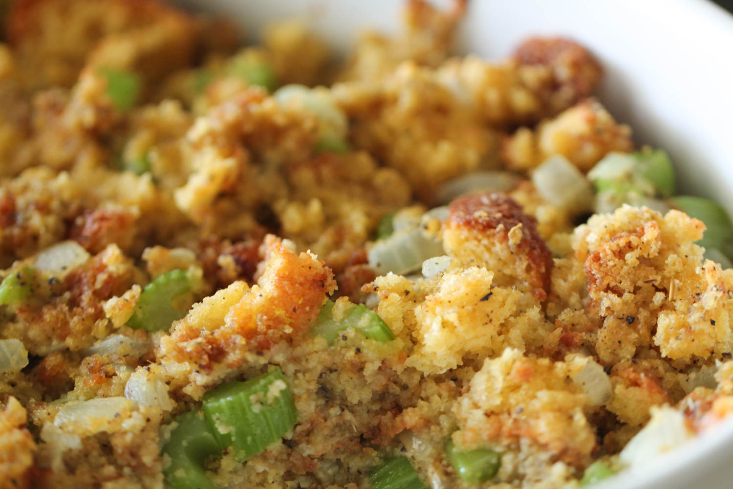 Homemade Corn Bread Stuffing in pan with close up image.