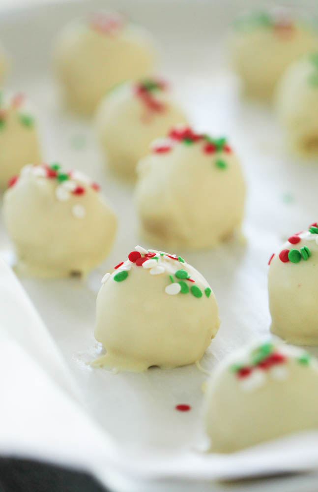 sugar cookie truffles sitting on a baking sheet topped with christmas sprinkles