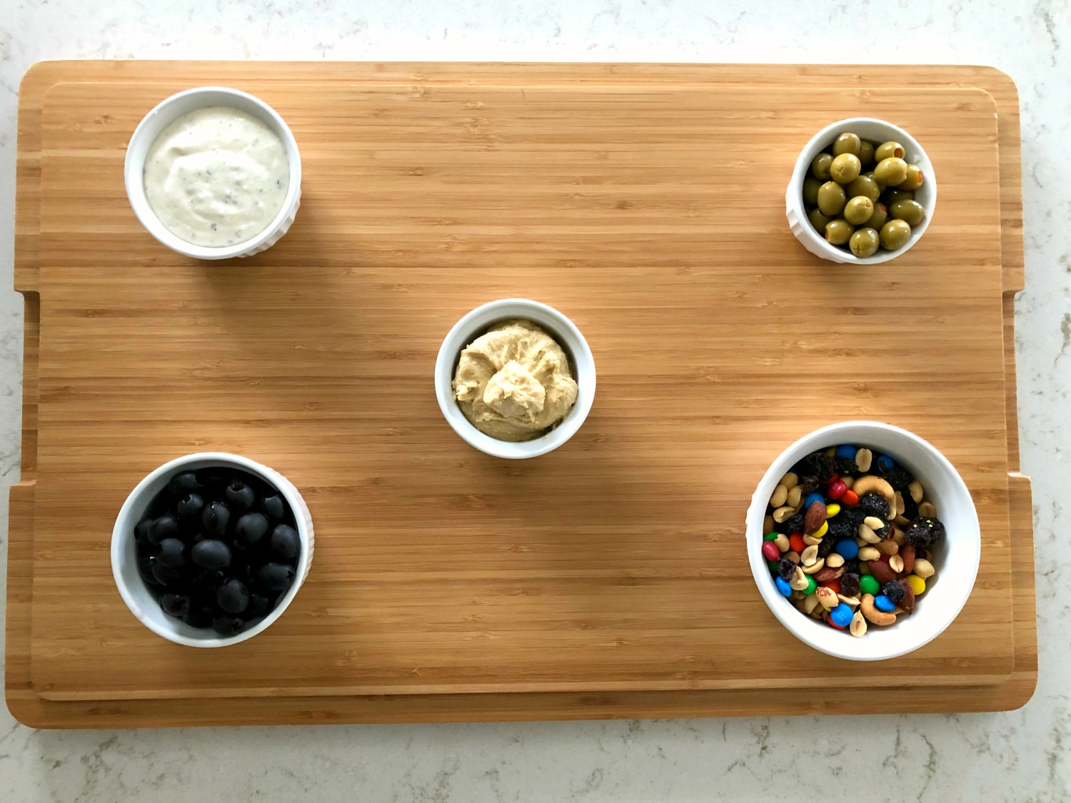 white bowls filled with hummus, ranch, olives, and trail mix spread out on a cutting board