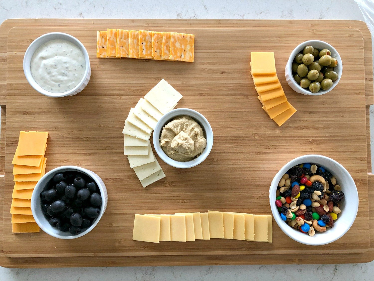 dips and olives in small white bowls with small squares of cheese surrounding them on a wooden cutting board