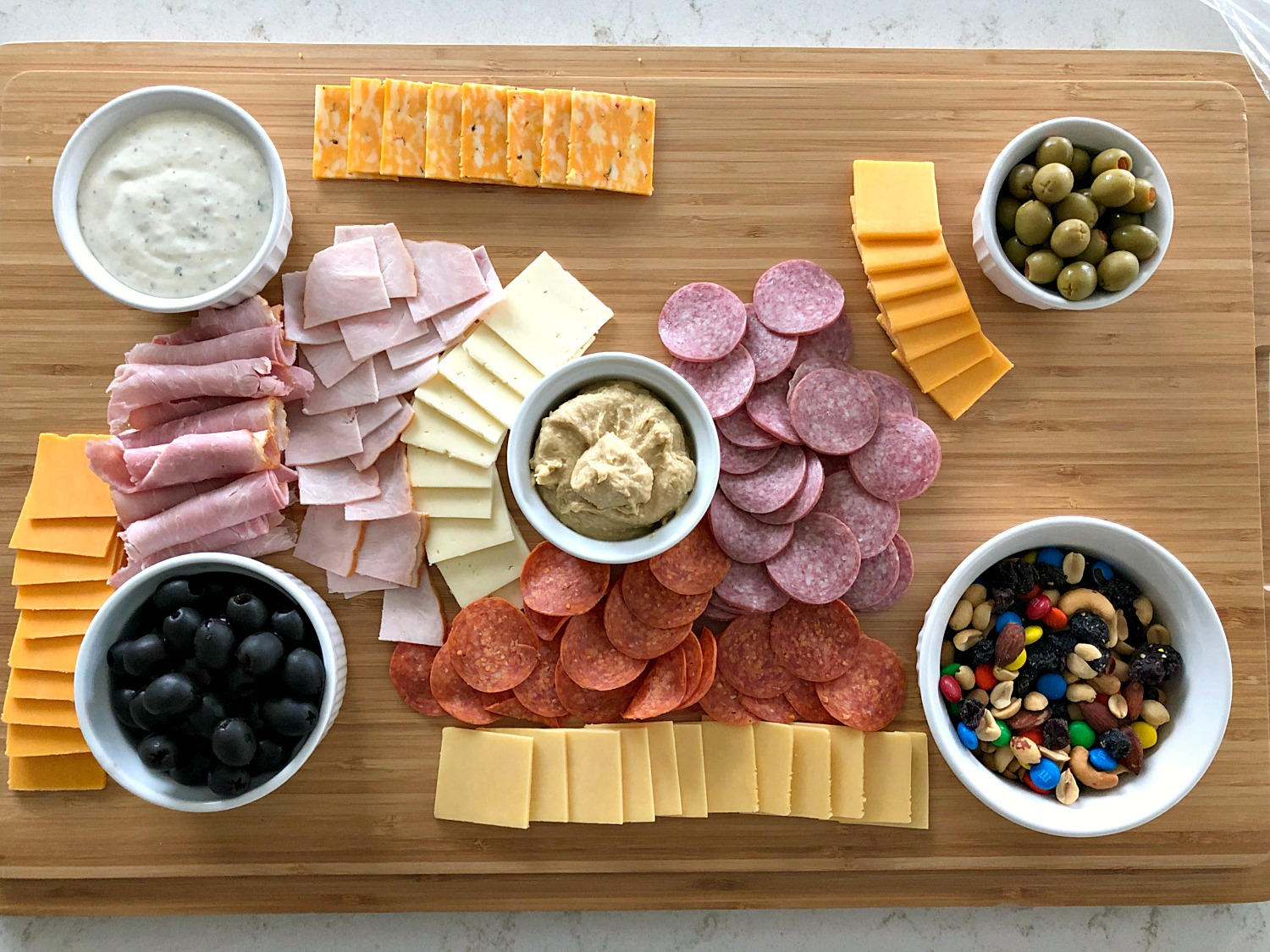 small pieces of ham and cheese with dips in white bowls spread out on a wooden cutting board