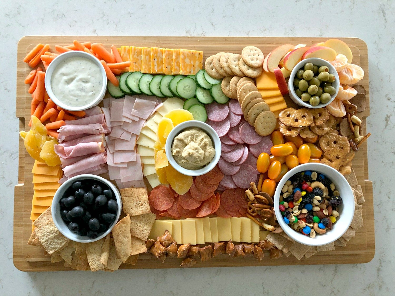 full charcuterie board with meats, cheese, olives, pretzels, pepperoni, fruits, and vegetables