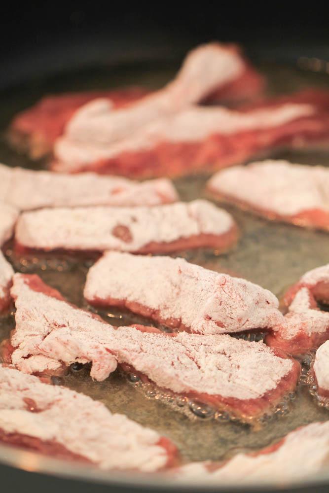Steak strips iin oil in sauté pan