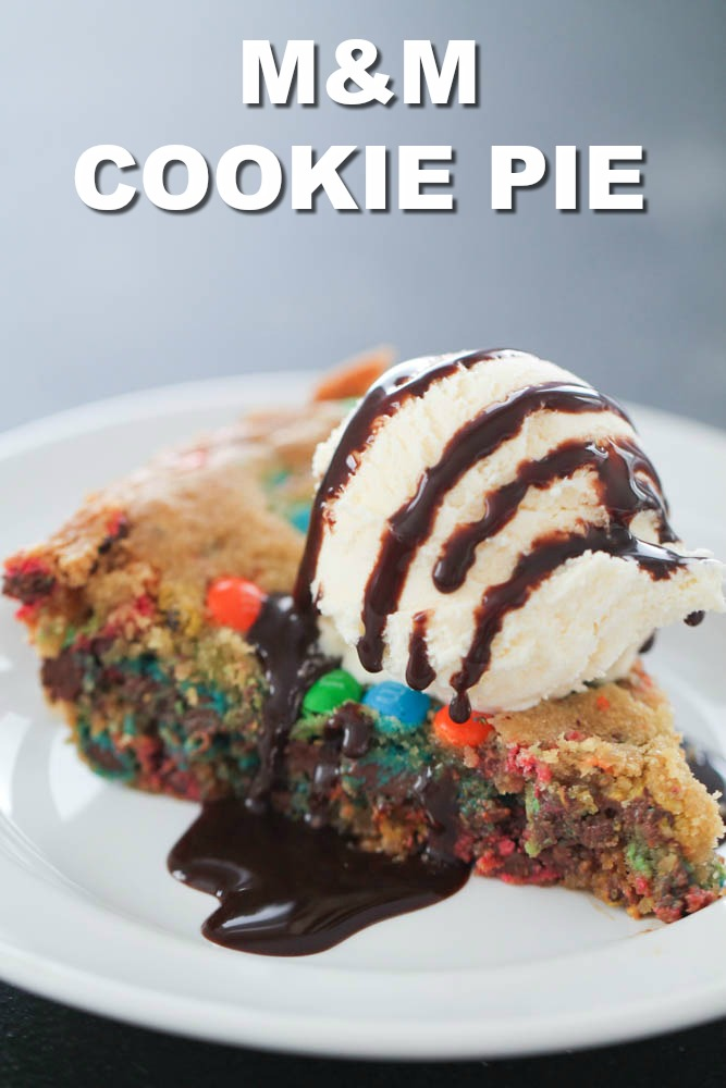 M&M Cookie Pie slice on a white plate with ice cream and chocolate sauce