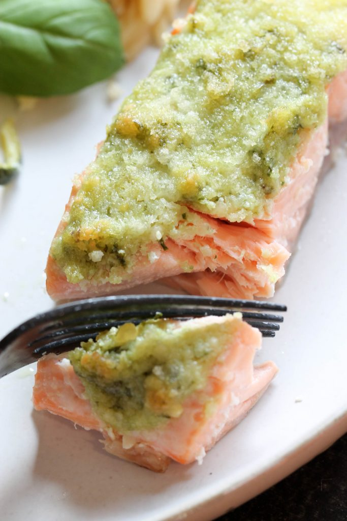 salmon filet with pesto on top being cut with a fork