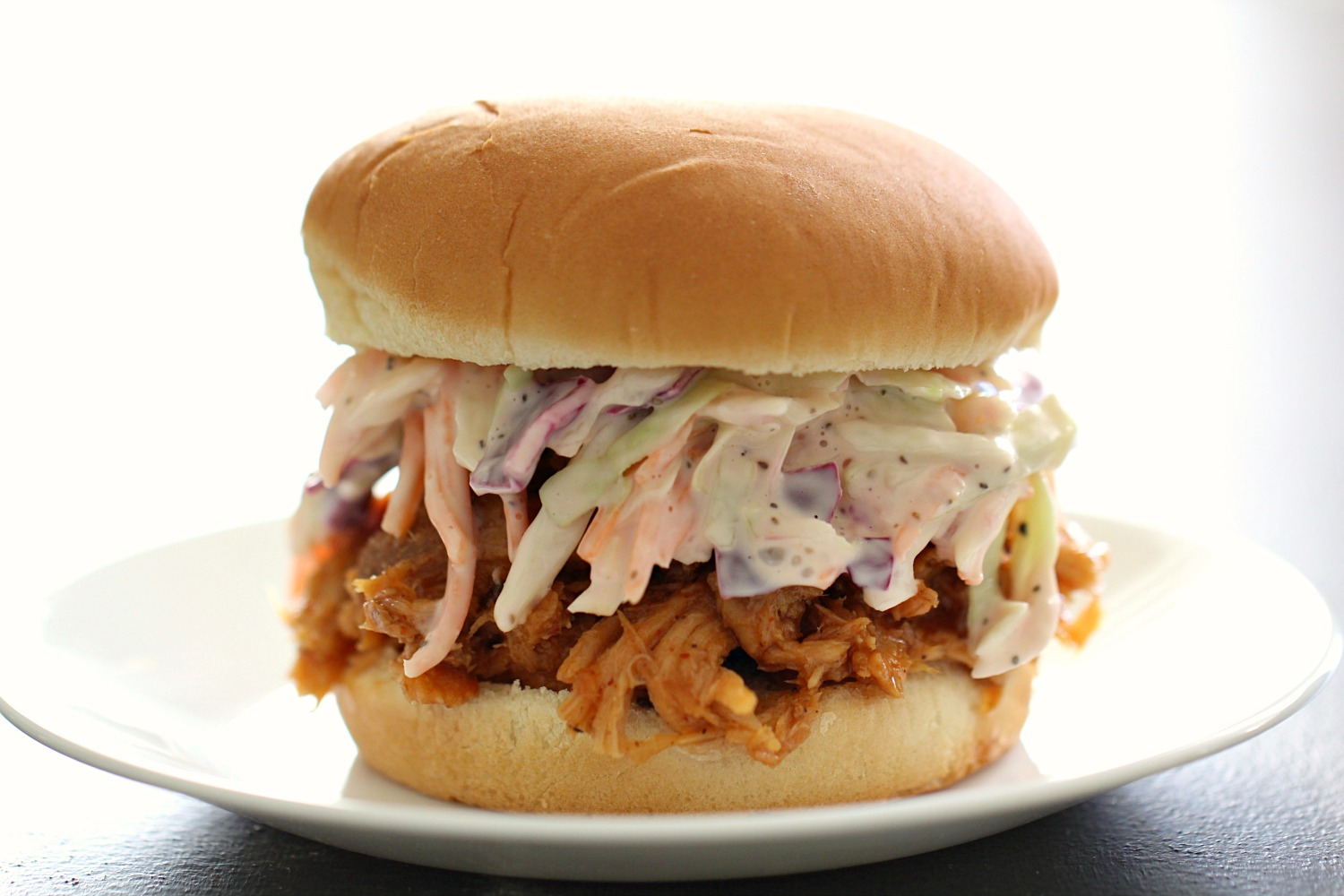 BEST Slow Cooker BBQ Pulled Pork and Coleslaw Sandwich on a white plate