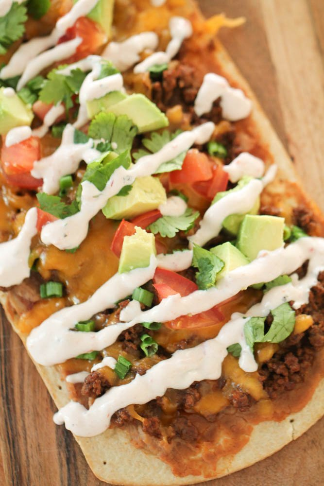 Cooked Flatbread Mexican Pizza drizzled with sour cream and topped with avocado and cilantro