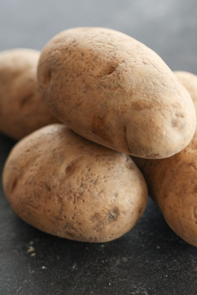russet potatoes stacked in a pile