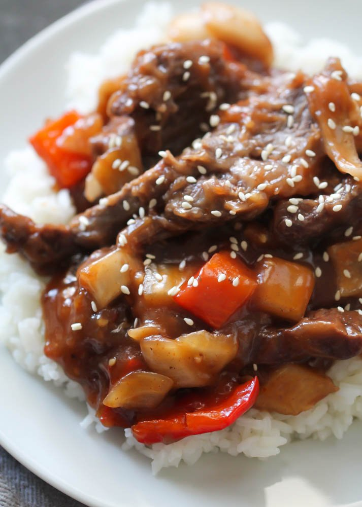 Slow Cooker Beijing Beef on top of rice on a white plate