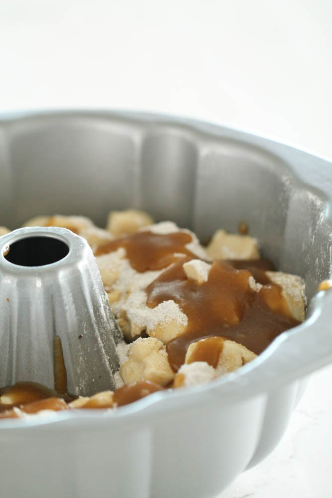 Layers of pecans, thawed rolls, pudding mixture and brown sugar and butter mixture in the bundt pan, ready to rise and then cook