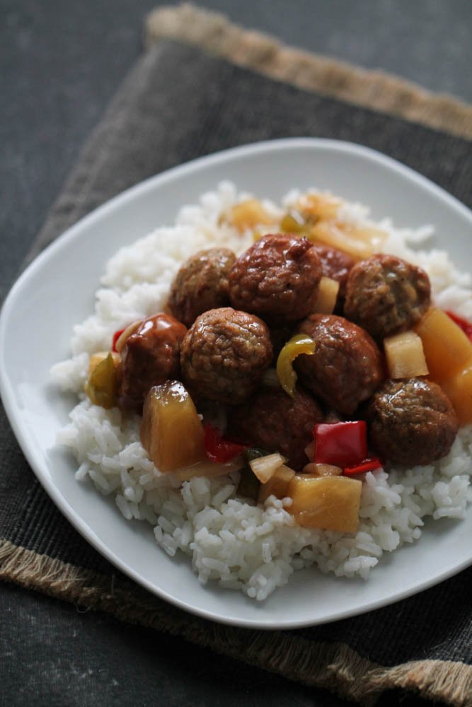 Slow Cooker Hawaiian Meatballs served over rice on a white plate