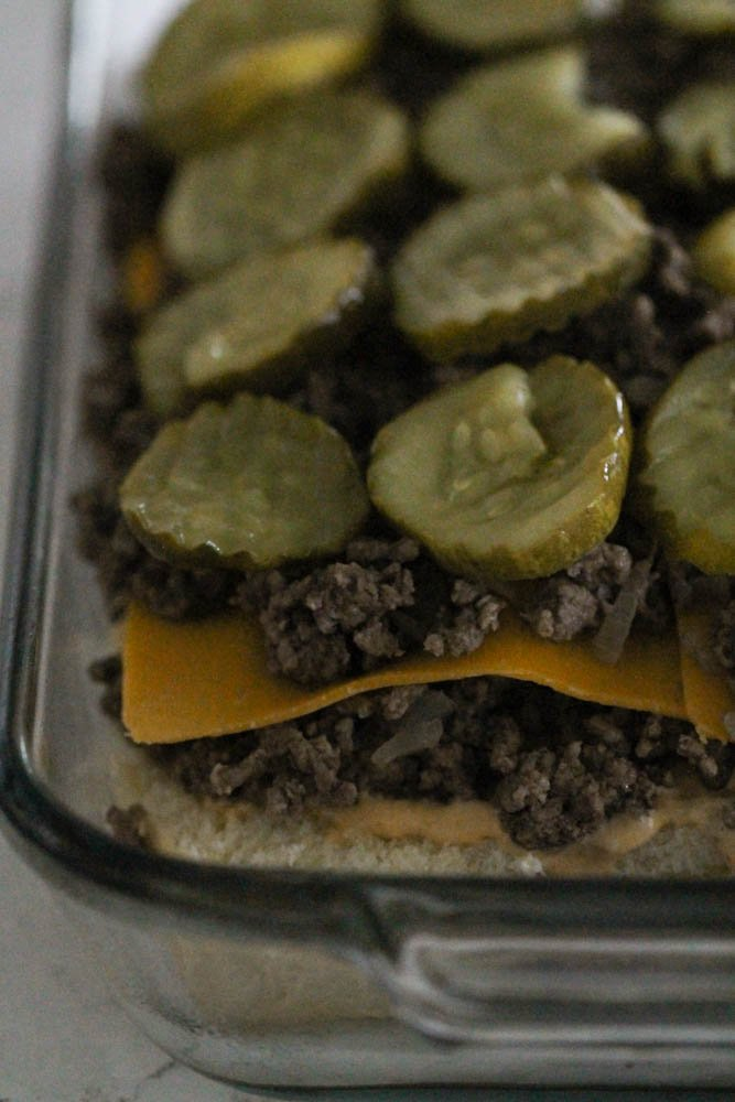 hambuurger on sliders topped with cheese pickles