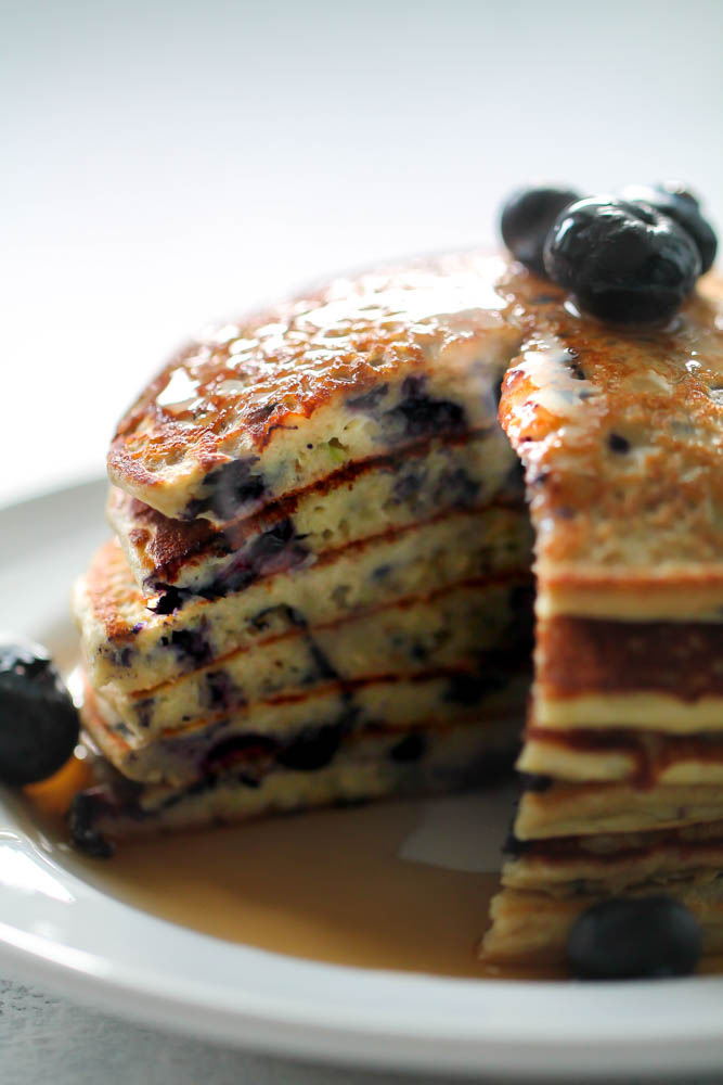 Blueberry Protein Pancakes stacked on a white plate with syrup on top