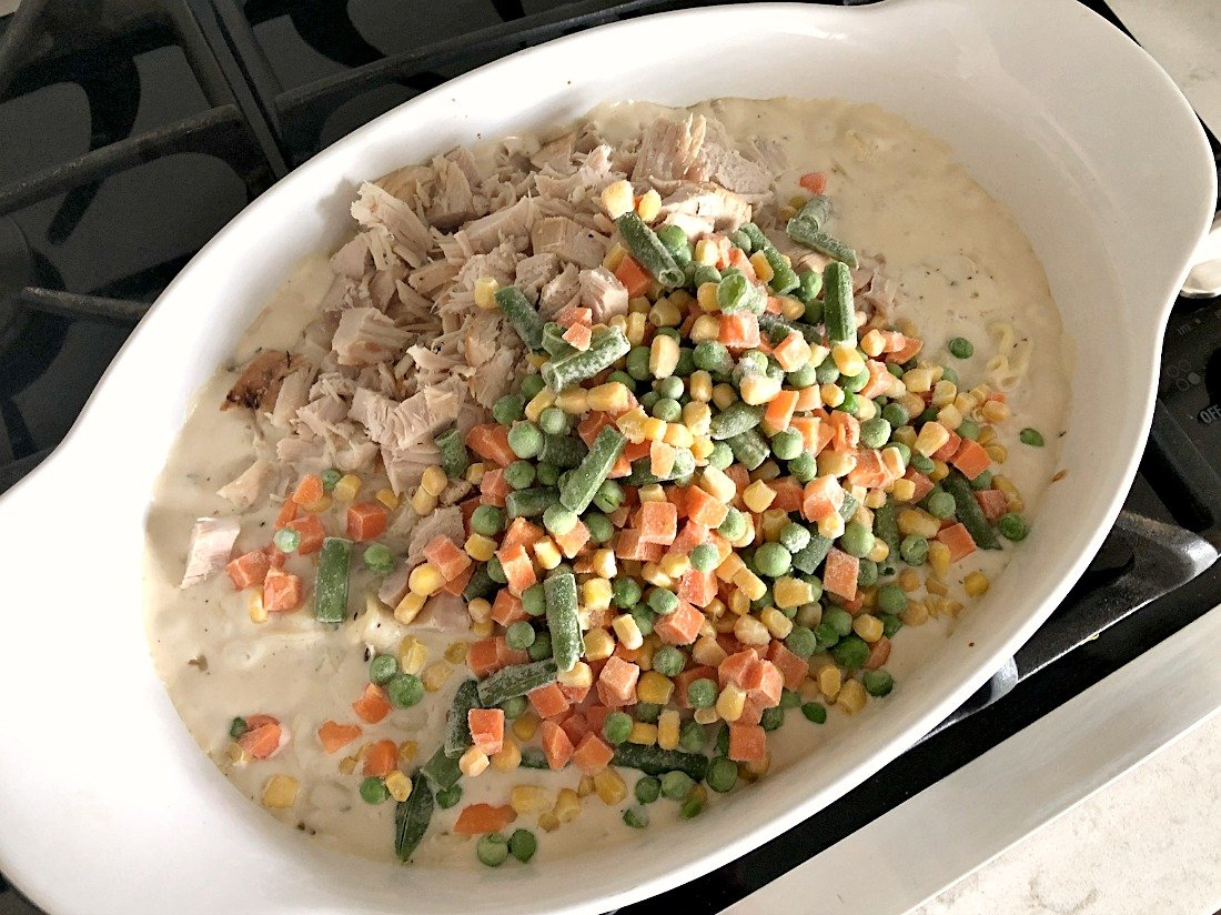 Frozen vegetables on top of chicken and sauce in casserole dish