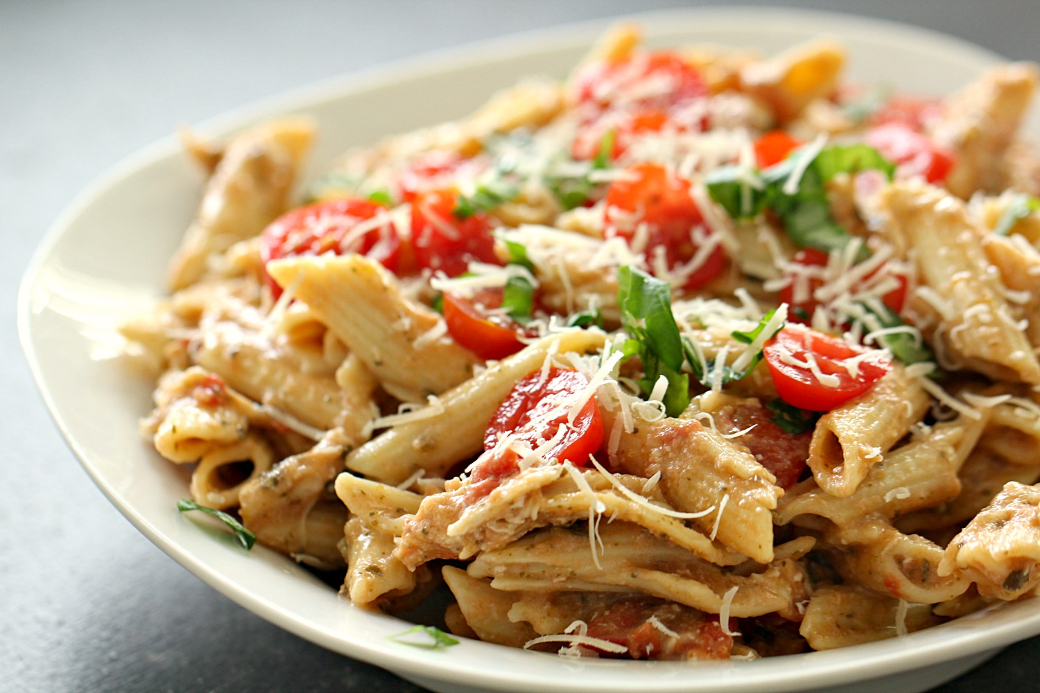 Slow Cooker Alfredo Pesto Chicken and Pasta on a white dinner plate topped with tomatoes and cheese