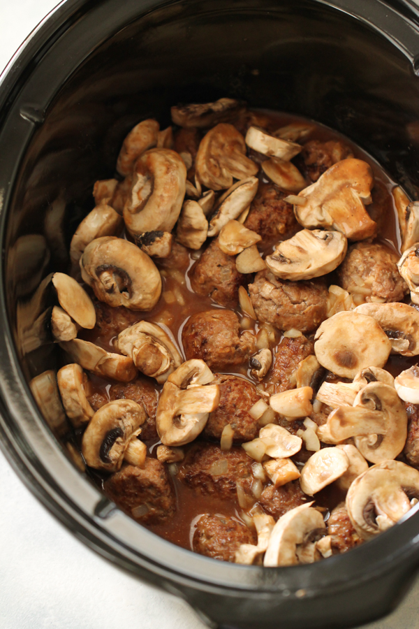 Salisbury Steak Meatballs in crockpot topped with sauce and mushrooms