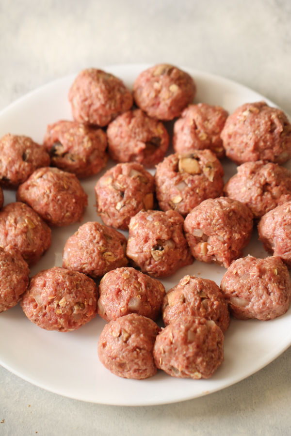 uncooked formed meatballs on white plate
