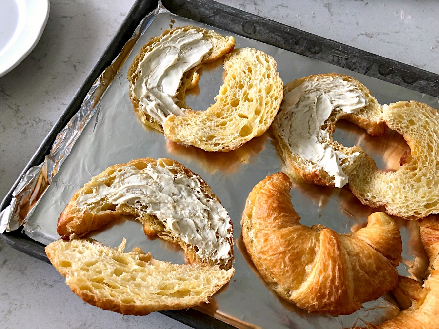 Croissants sliced with cream cheese spread