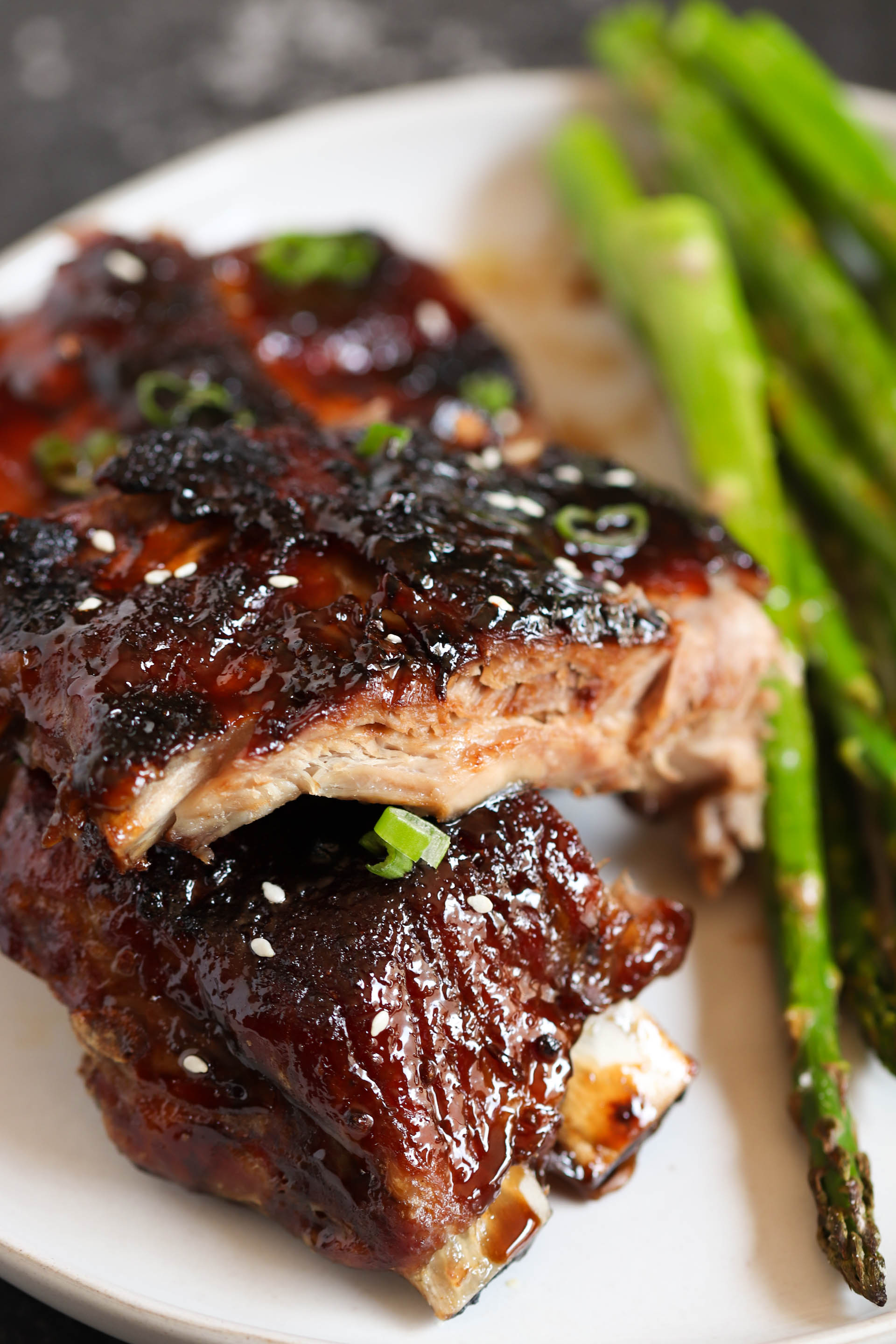Sticky Asian Ribs with asparagus on a plate
