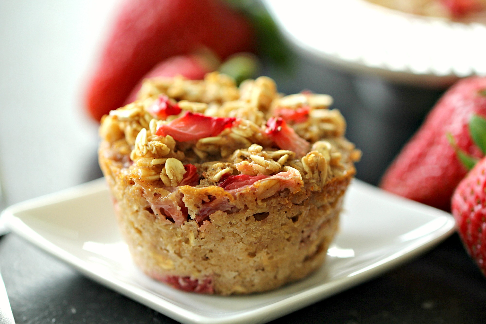 single baked oatmeal muffin cup topped with strawberries on a white plate