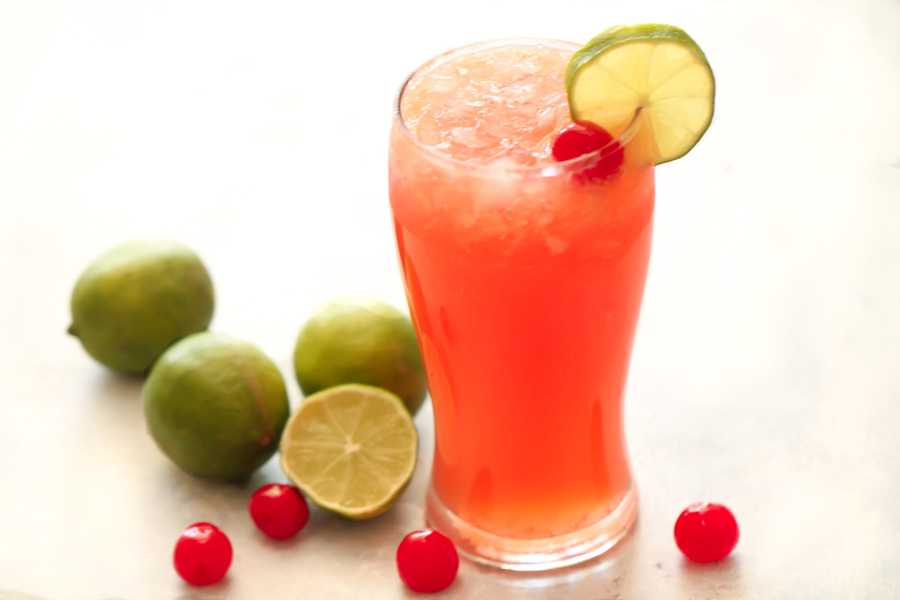 Cherry LImeade in a glass with Limes and Cherries