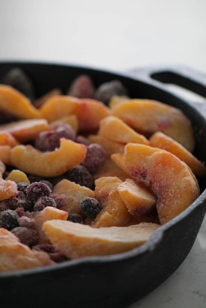 Peach and Berry Crisp in a skillet without the crisp mixture on top