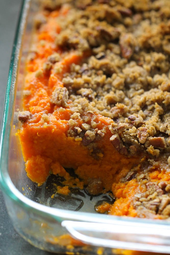 sweet potato casserole with brown sugar and pecan topping with a piece taken out