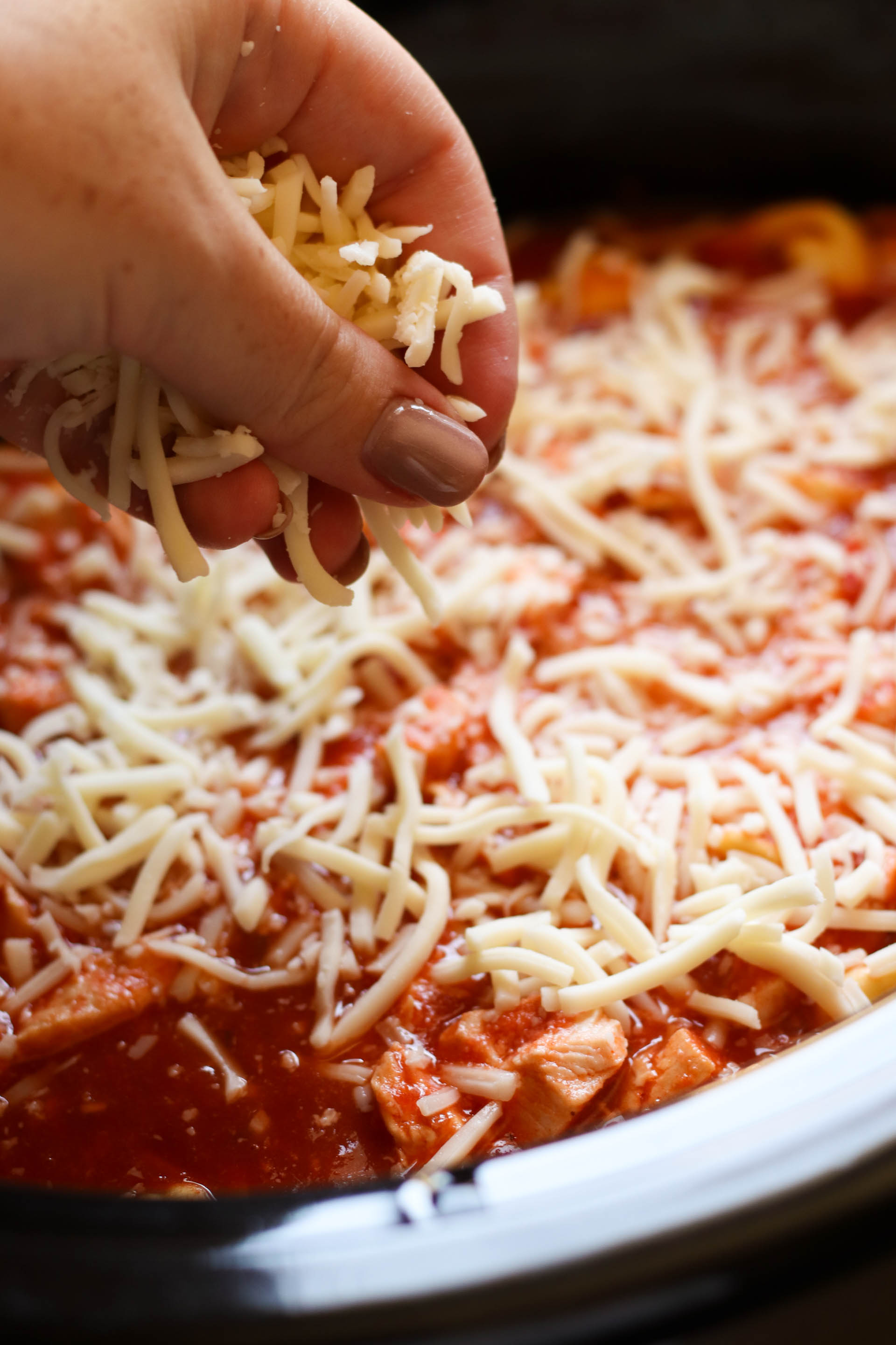 Topping slow cooker mixture with shredded cheese