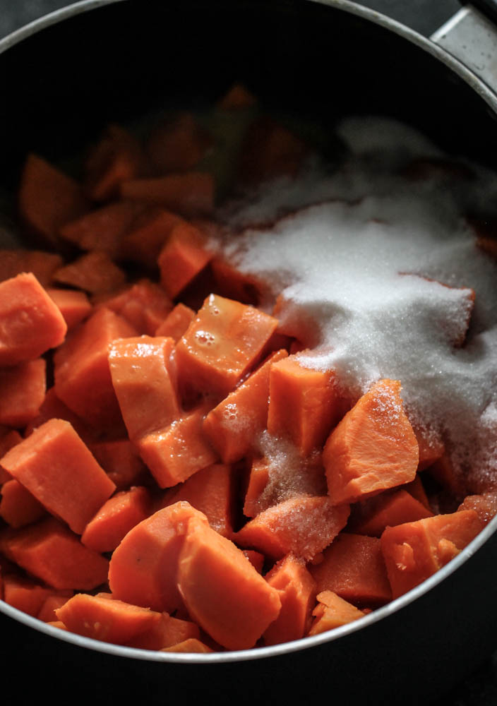 sweet potatoes diced in a pot with sugar on top