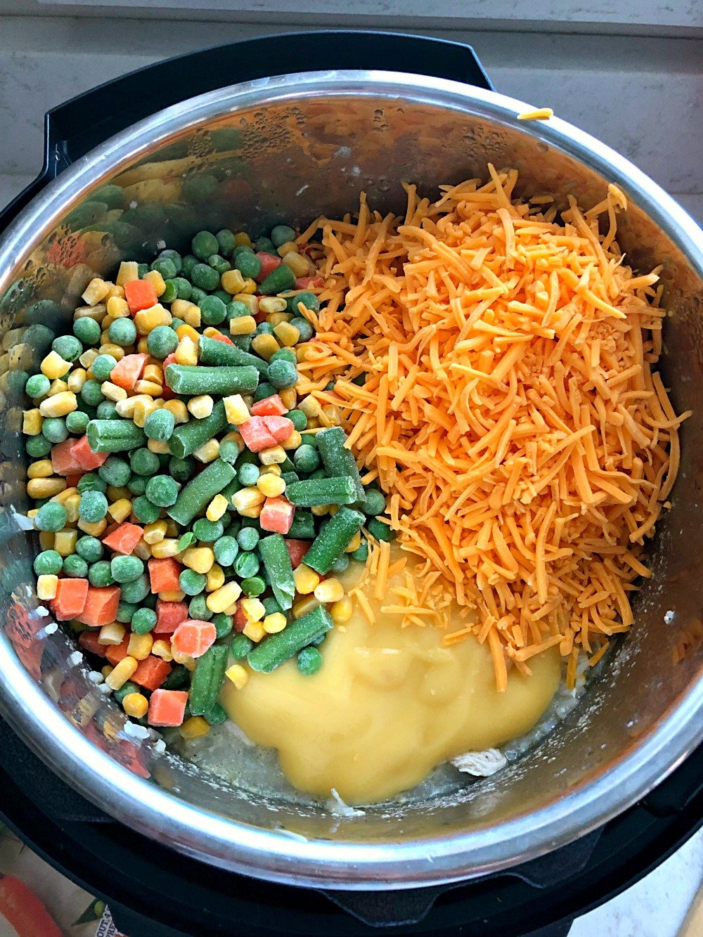 frozen vegetables, cheese, and chicken soup dumped into an instant pot