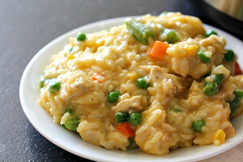 plate of cheesy chicken and rice with peas, carrots and green beans