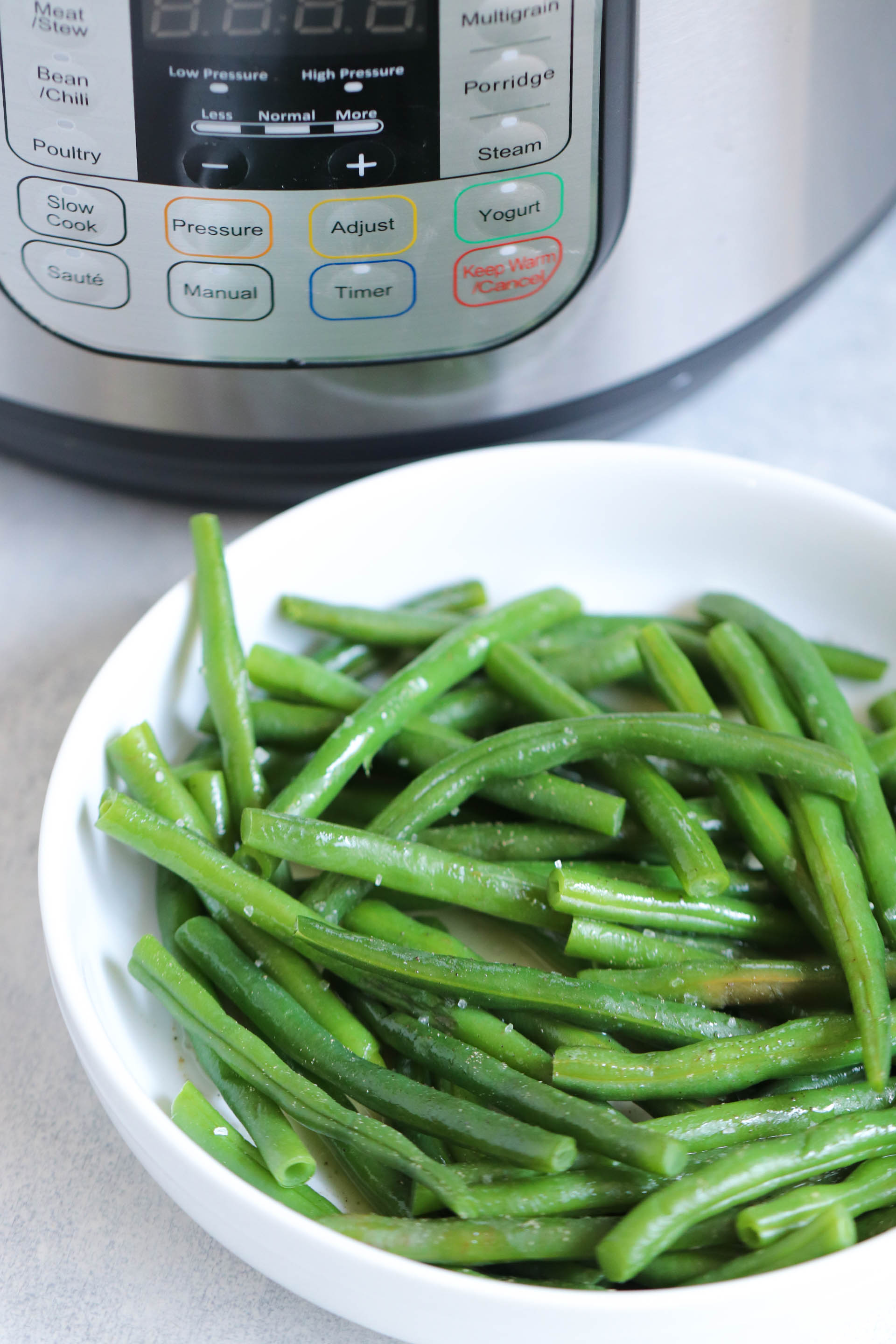 Cooked green beans in a bowl next to an Instant Pot