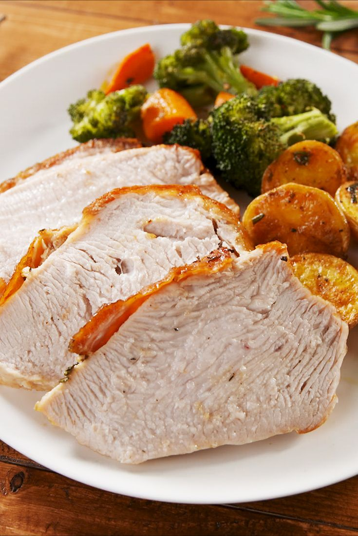 cooked and sliced turkey breast on a white plate with broccoli and sweet potatoes